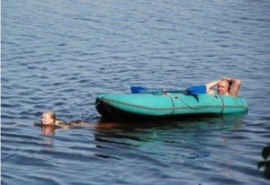 A man is relaxing in a small boat that is being pulled by a swimming woman.