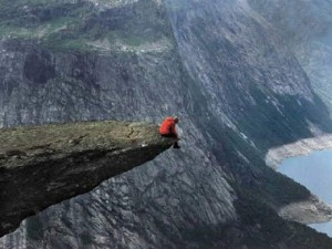 A man sitting on the edge of a cliff thinking if there is anywhere more beautiful.