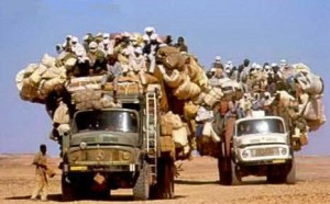 Two lorries both full of people. Each person has a bag.