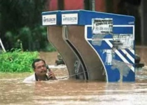 A man is using a phone while the flood water around him is rising.