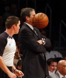 A basketball coach has been hit in the face with a ball. The photo captures the exact moment it happened.