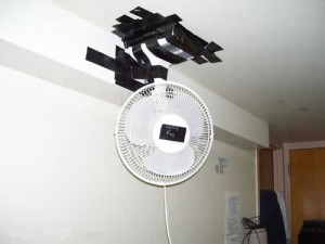 A cooling fan has been fixed to the ceiling with black tape.