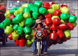A man is riding his motorbike while carrying many, many plastic items. I.e. buckets.