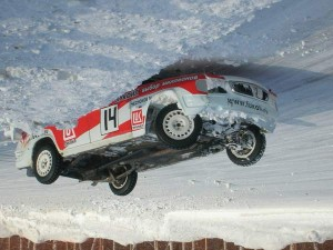 A car is lying on its roof in the snow, but the photo is upside down giving an irregular perspective.