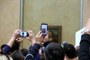 Many people with a lot of cameras photographing the Mona Lisa making it difficult to see the painting.