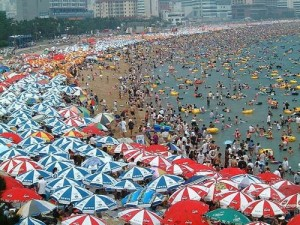 Many umbrellas and a lot of people on a beach but not much sand.