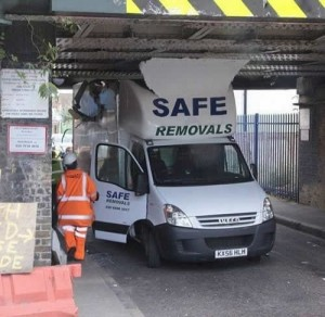 A van from a company called safe removals has crashed into a low bridge.
