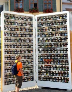 A man is standing next to a giant fridge containing some beer.