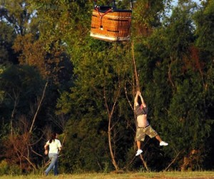 A hot-air balloon has escaped and a man is hanging under it.