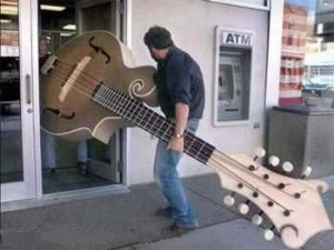 A man carrying a very big guitar into a shop.