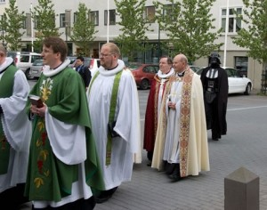 Alt text: A man in a Darth Vader suit is walking behind a line of priests.