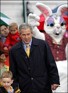 A person in a rabbit suit is standing behind George Bush and waving.