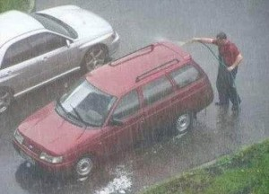 A man is cleaning his car with a hose pipe, but there is also very heavy rain.