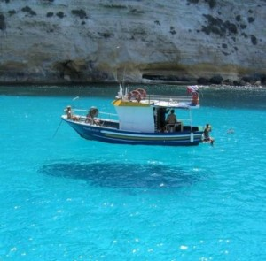 A boat is sailing on beautiful clear blue water giving the impression it is floating above the water.