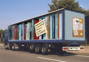 A lorry has books painted on the side. Every book is very big.