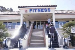 Stairs and escalator up to a fitness centre. Everyone is using the escalator.