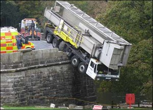A large lorry is hanging over the side of a bridge in English village.