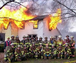 A large group of firemen are posing for a group photo in front of a house that is on fire.
