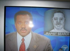 A TV newsreader is talking about a police Photofit of a criminal. The Photofit looks like the newsreader.