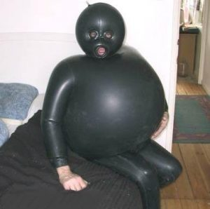 A funny picture of a person who is wearing an inflated S&M rubber suit. She has a question about using who in English.